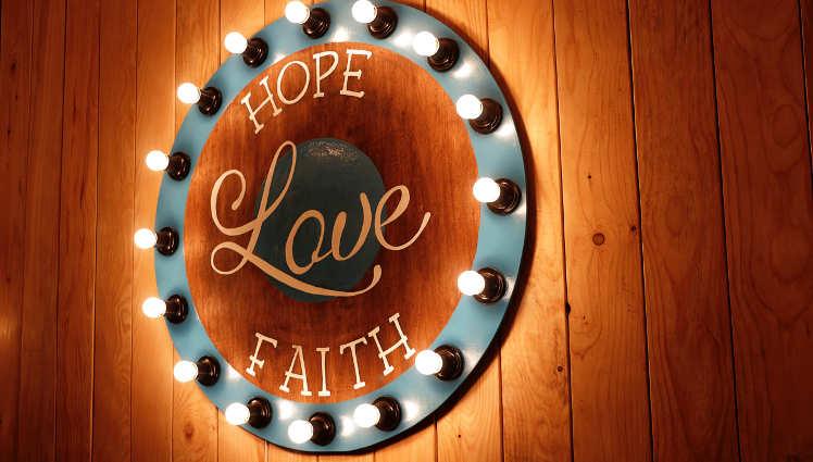 a sign with words Hope, Love, and Faith