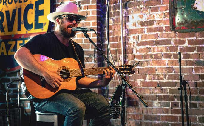 a man singing while playing guitar